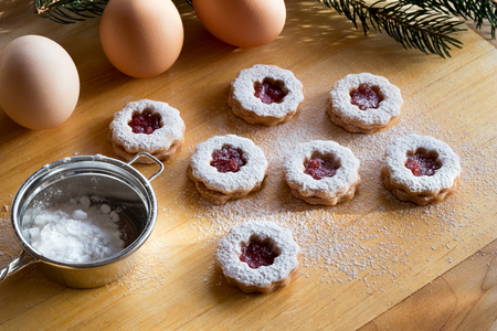 Trraditional Linzer Christmas cookies dusted with sugar, with a sifter and eggs in the background