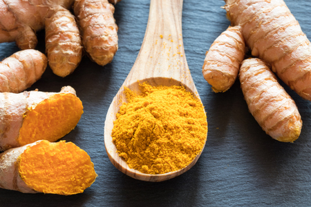 96030327-turmeric-powder-and-fresh-turmeric-root-on-a-dark-background.jpg?ver=6