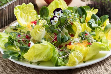 Vegetable salad with fresh kale and broccoli microgreens, lettuce, corn salad, avocado, orange, pomegranate and edibe flowers