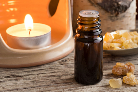 A dark bottle of frankincense essential oil with frankincense resin and an aroma lamp