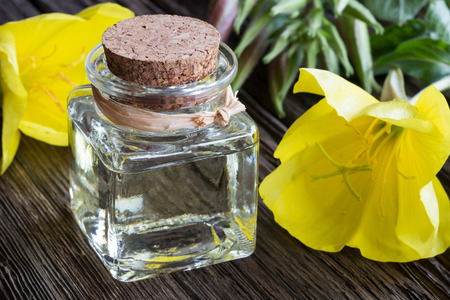 A bottle of evening primrose oil with yellow evening primrose flowers Stock Photo