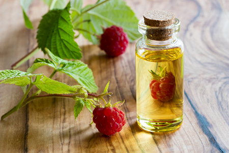 Fresh raspberries with a bottle of raspberry seed oil on a table