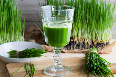 A glass of wheatgrass juice with freshly harvested wheatgrass on a wooden table