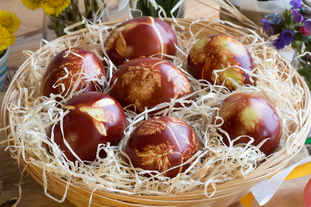 Easter eggs dyed with onion peels, with a pattern of fresh herbs, in a wicker basket