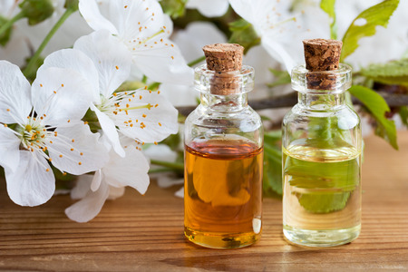 Bottles of essential oil with white cherry blossoms