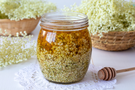 A jar filled with fresh elder flowers and honey, to prepare homemade herbal syrup