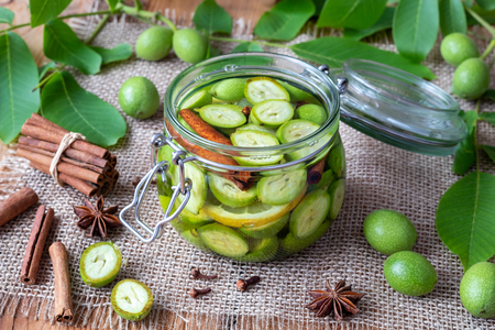 A glass jar filled with unripe walnuts, alcohol and spices, to prepare homemade tincture