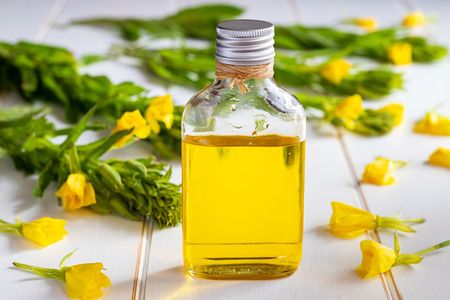 A bottle of evening primrose oil and fresh blooming plant on a white background Stock Photo