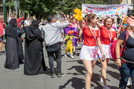 PRAGUE, CZECH REPUBLIC - JULY 1, 2018: People parading at Sokolsky Slet, a once-every-six-years gathering of the Sokol movement - a Czech sports association. Women in burqas greet the parade. 新聞圖片