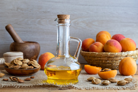 A bottle of apricot kernel oil with fresh ripe fruit Archivio Fotografico