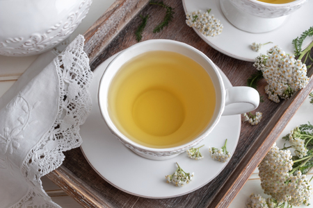 Yarrow tea in a white vintage cup with fresh twigs
