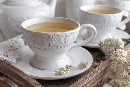 Yarrow tea in white vintage cups with fresh twigs
