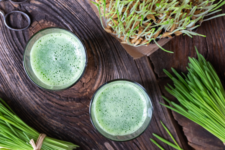 Two glasses of barley grass juice with freshly harvested blades, top view