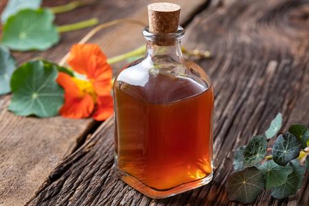 A bottle of nasturtium tincture with fresh bloomingTropaeolum majus plant