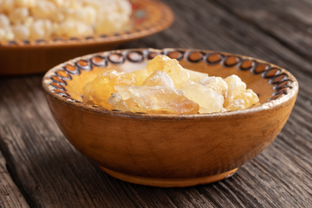 Frankincense resin crystals in a wooden bowl