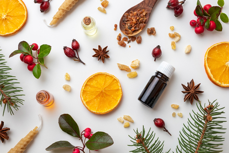 Bottles of essential oil on a white Christmas background with frankincense, myrrh, wintergreen and various winter spices