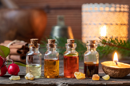 Christmas collection of essential oils with frankincense, wintergreen and candles Stock Photo