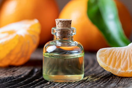 A bottle of citrus essential oil with fresh tangerines on a table