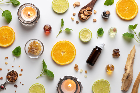 Bottles of essential oil with fresh citrus fruit, melissa, myrrh, white sandalwood and other ingredients Stock Photo