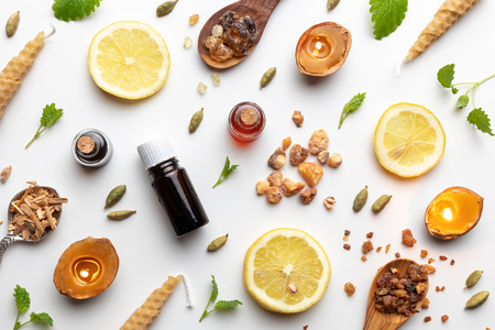 Bottles of essential oil with frankincense, cardamon, melissa, fresh lemon and other ingredients on a white background Stock Photo