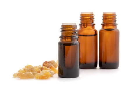 Bottles of essential oil with frankincense resin on a white background