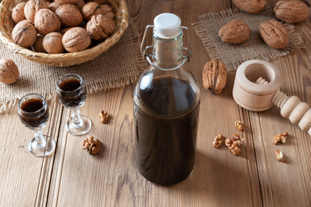 A bottle of homemade nut liqueur with walnuts on a table