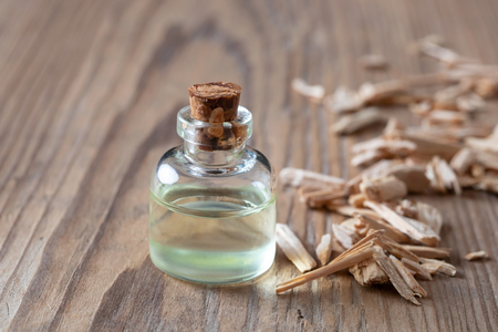 A bottle of essential oil with pieces of cedar wood on a table