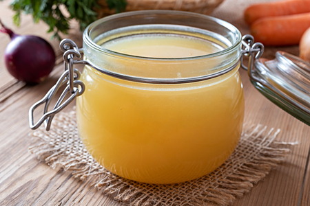 Chicken bone broth in a glass jar, with onions and carrots in the background Imagens
