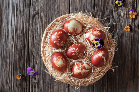 Easter eggs dyed with onion peels with a pattern of fresh herbs in a wicker basket, with colorful pansies and copy space, top view