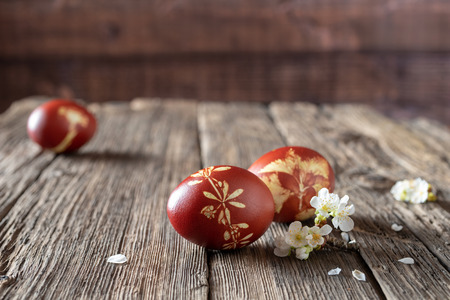 Easter eggs dyed with onion peels with a pattern of fresh herbs, on a rustic background