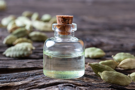 A bottle of essential oil with whole cardamon seeds