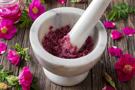 Fresh Rugosa rose flowers crushed with cane sugar in a marble mortar