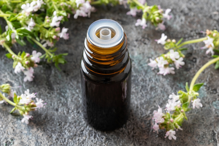A bottle of essential oil with blooming thyme twigs Reklamní fotografie