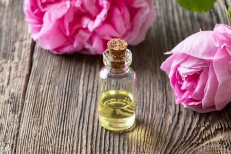 A bottle of essential oil with fresh rose de mai flowers Zdjęcie Seryjne