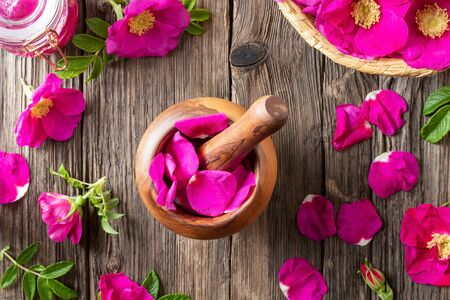 Fresh Rugosa rose petals in a wooden mortar, top view