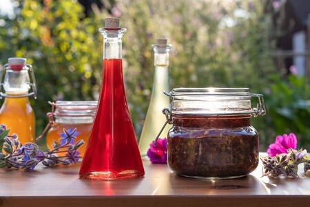 A bottle of red oil made from St. Johns wort flowers, with herbal syrups in the background, photographed in a garden