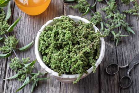 Nettle seeds in a white bowl, with honey in the background Archivio Fotografico