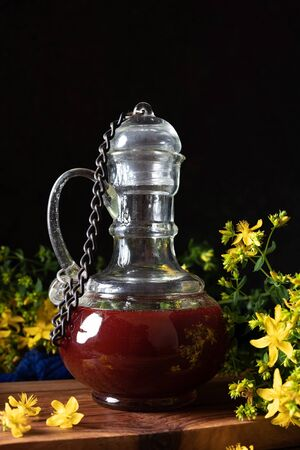 A bottle of red oil made from St. Johns wort flowers - dark photography Stok Fotoğraf