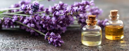 Panoramic header of essential oil bottles with fresh lavender flowers