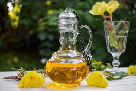 Evening primrose oil in a beautiful bottle with fresh flowers