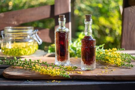 Two bottles of herbal tincture with fresh agrimony flowers in the background