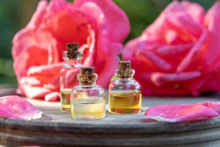 Bottles of essential oil with rose flowers in the background