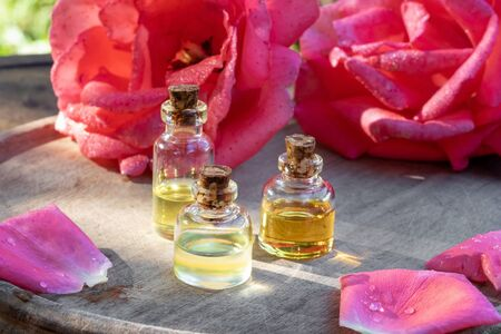Three bottles of essential oil with fresh roses in the background