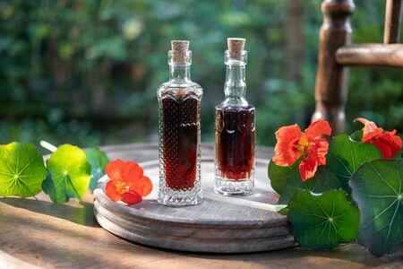 Bottles of herbal tincture with fresh bloomingTropaeolum majus plant