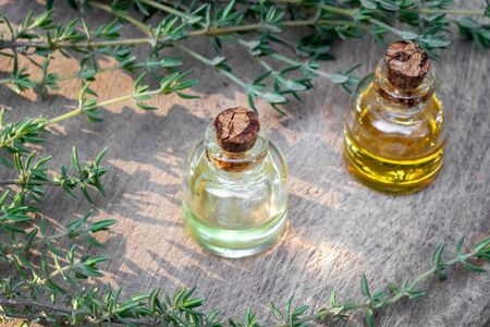 Bottles of essential oil with fresh thyme twigs