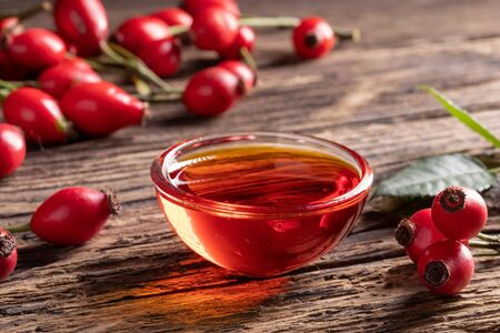 A bowl of rose hip seed oil with fresh rose hips