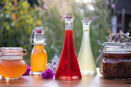 Homemade oil made from St. Johns wort flowers, with various herbal syrups and flowers in the background