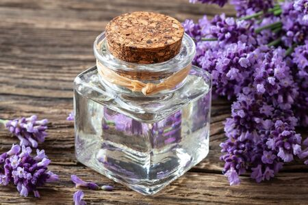 A bottle of essential oil with fresh blooming lavender twigs on a table 版權商用圖片