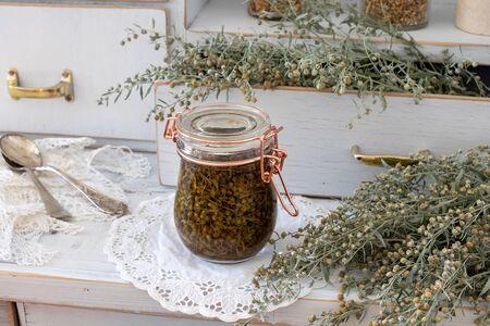 A jar of wormwood tincture with fresh Artemisia Absinthium plant on a white cupboard 版權商用圖片