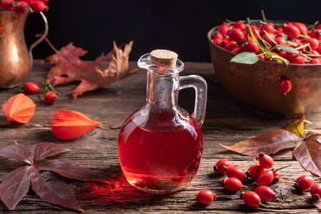 A bottle of rose hip seed oil with fresh berries and autumn leaves